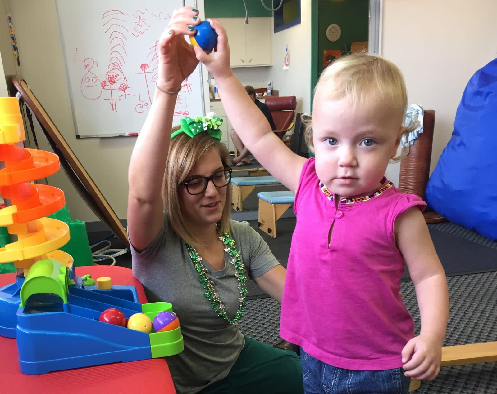 Little girl reaching for a ball working with her therapist