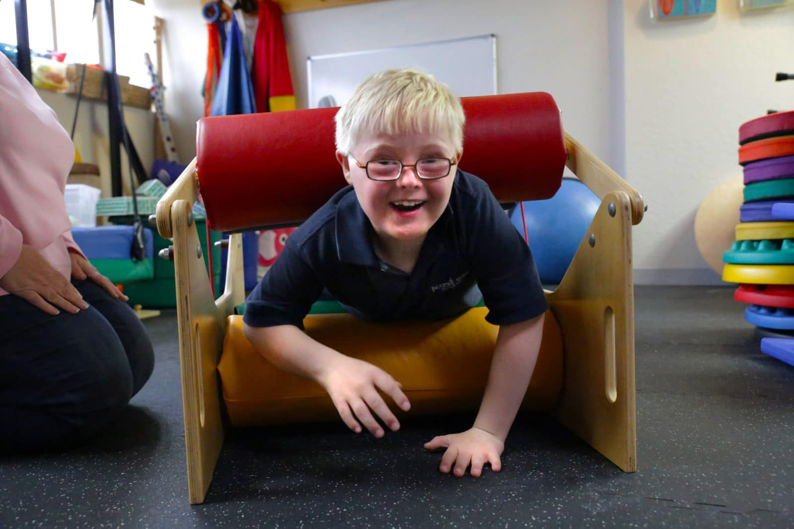 Little boy crawling through objects with his Occupational Therapist